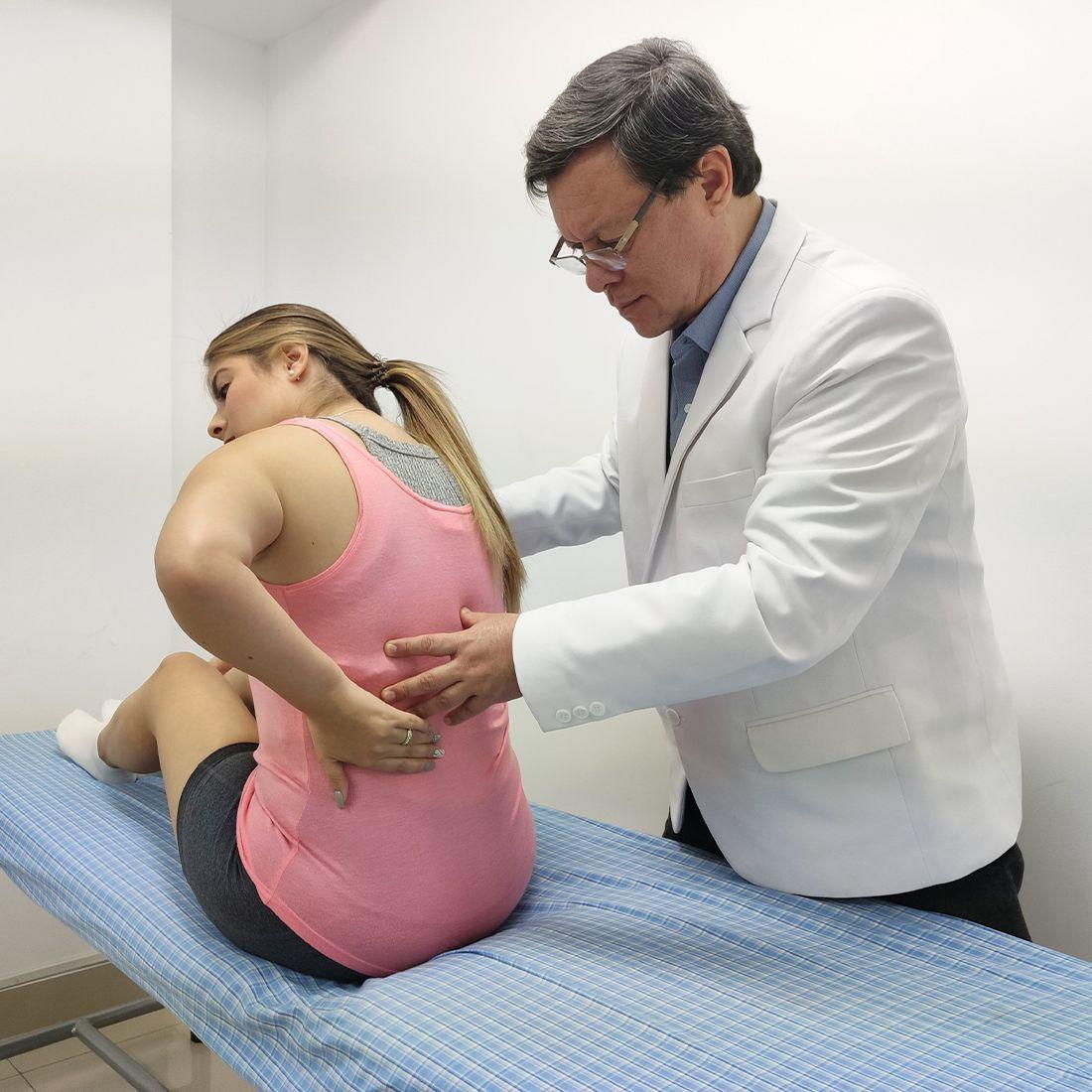 medico evalua espalda a paciente con estenosis lumbar